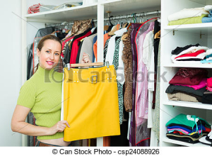 Smiling ordinary woman choosing apparel on shelves at store